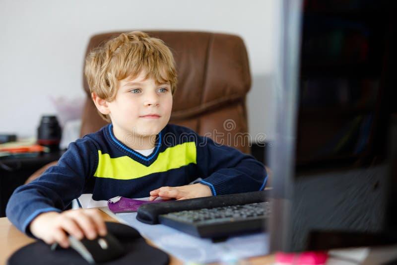 Menino da criança que faz trabalhos de casa da escola no caderno do computador Criança saudável feliz que procura a informação no fotografia de stock