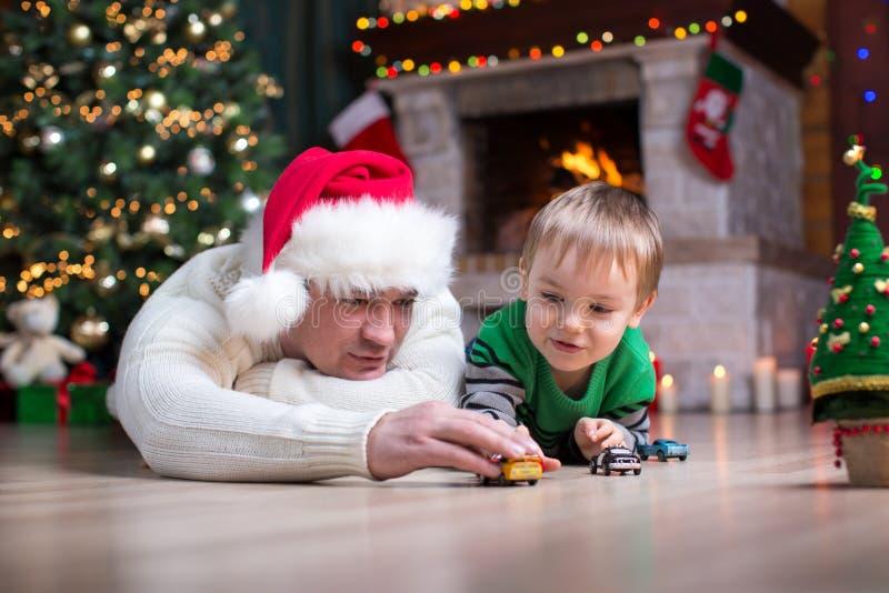 Menino da criança que joga carros do brinquedo com seus pais sob a árvore de Natal imagens de stock royalty free