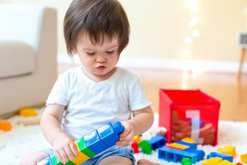 Menino da criança que joga com seus brinquedos foto de stock royalty free
