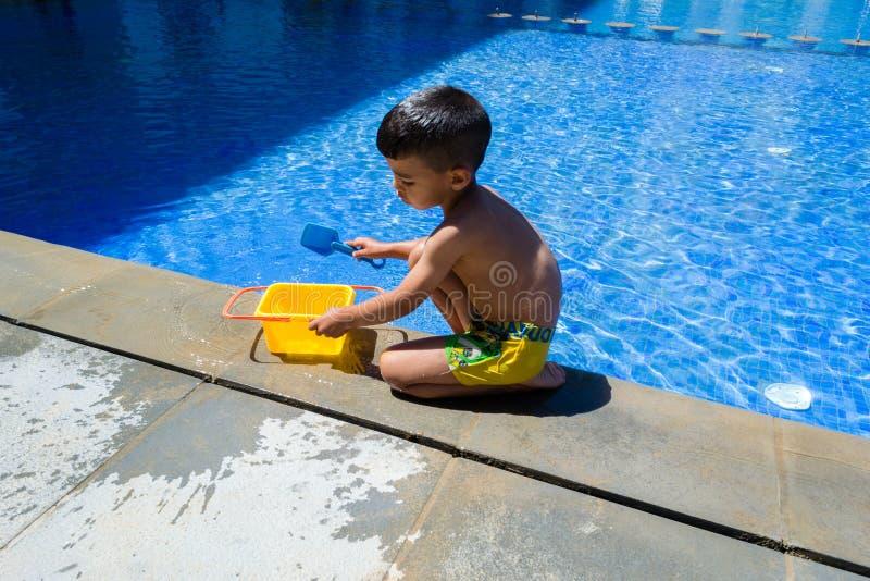 Menino da criança que joga com seus brinquedos na borda de uma piscina foto de stock