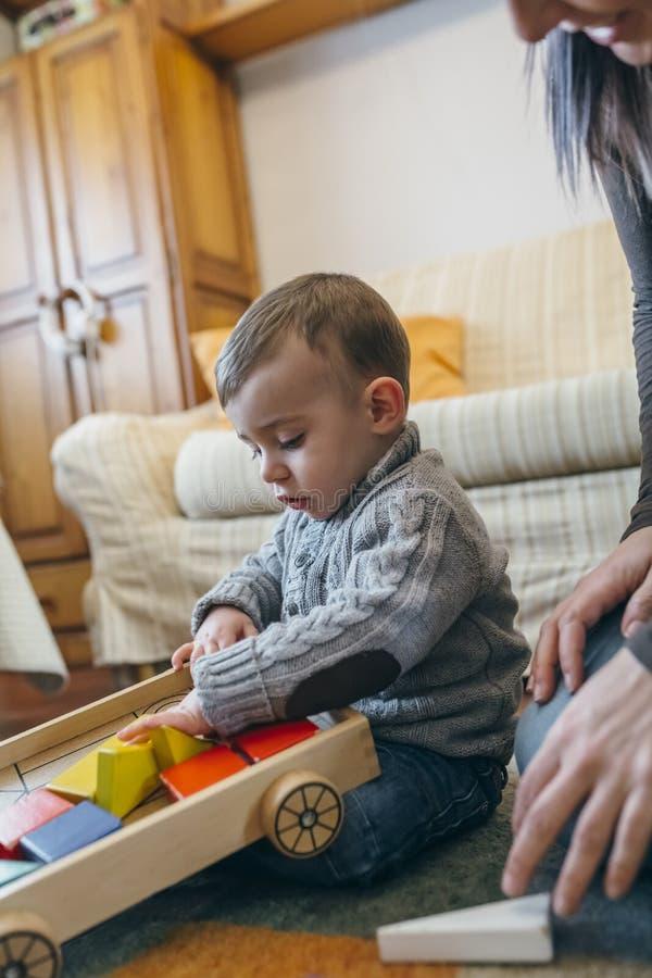 Menino da criança que joga com uma construção de madeira do jogo fotografia de stock
