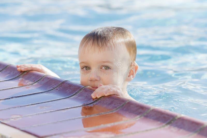 Menino da criança que joga em uma associação de água morna durante o inverno fotografia de stock royalty free