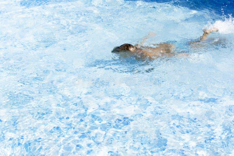Menino da criança que mantém a respiração subaquática na piscina ensolarada Aprendizagem nadar fotografia de stock