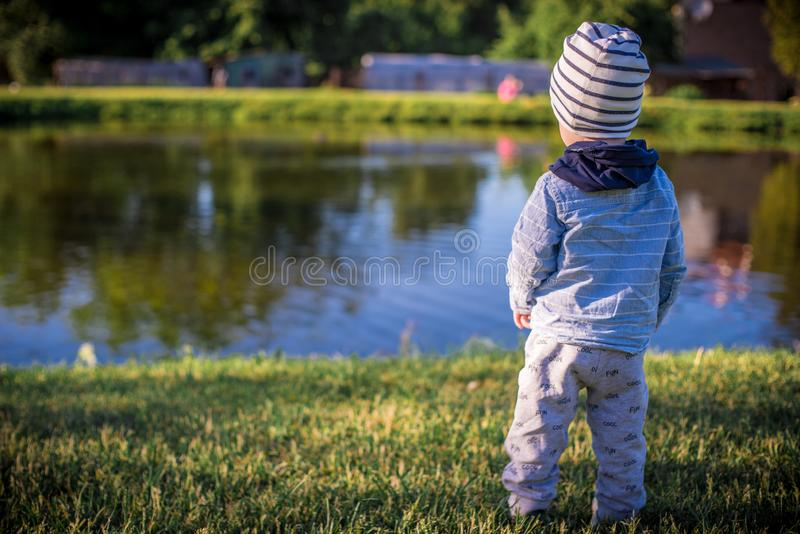 Menino da criança que olha à água do lago fotos de stock