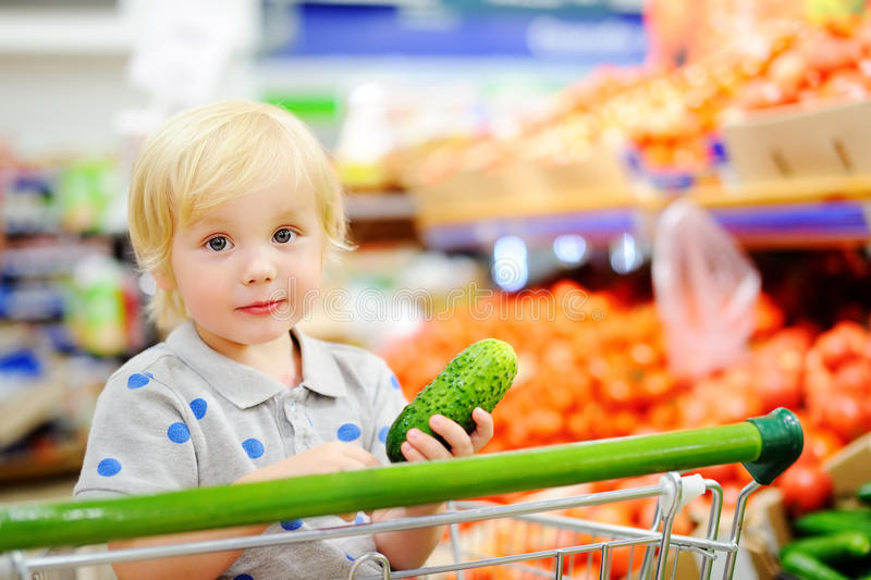 Menino da criança que senta-se no carrinho de compras em uma despensa ou em um supermercado fotografia de stock
