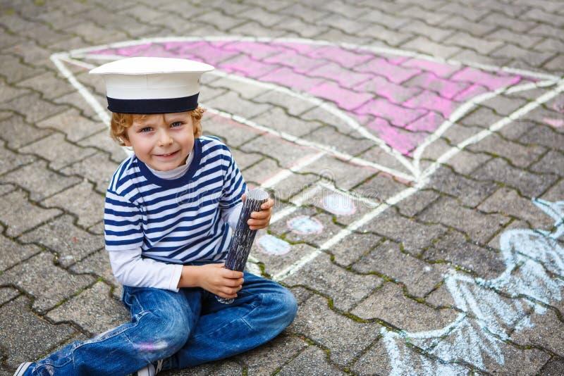 Menino da criança que tem o divertimento com o desenho da imagem do navio com giz imagens de stock