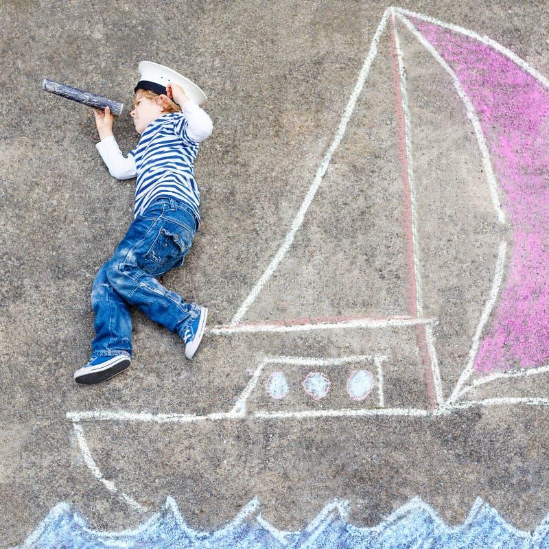 Menino da criança que tem o divertimento com o desenho da imagem do navio com giz fotografia de stock royalty free