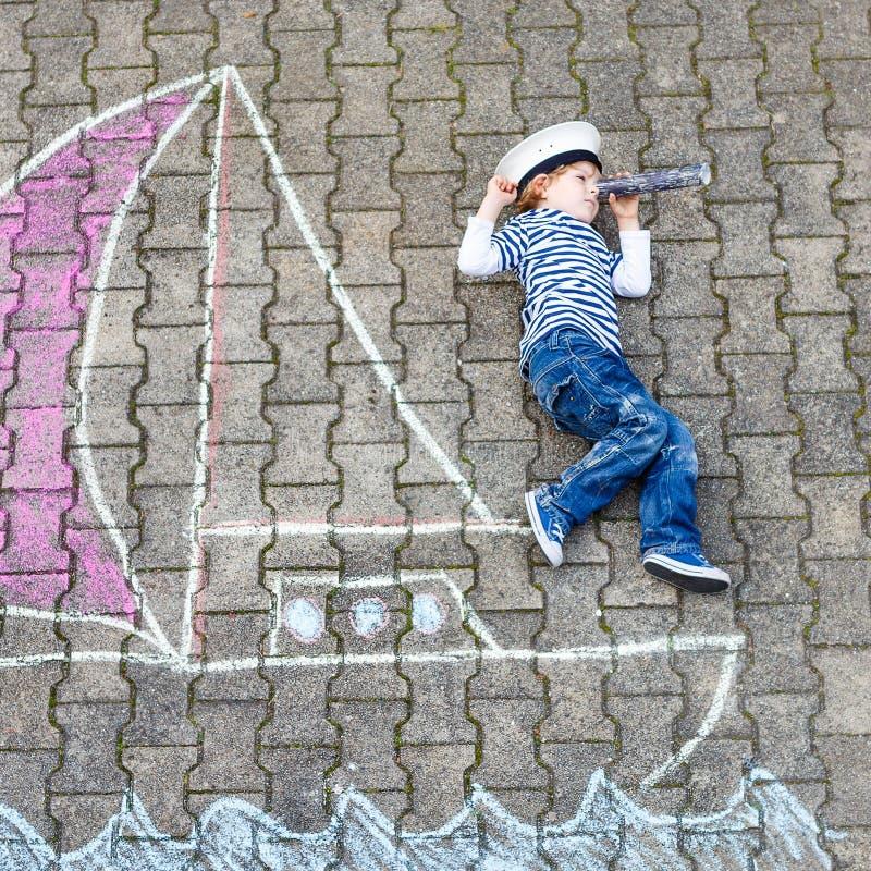 Menino da criança que tem o divertimento com o desenho da imagem do navio com giz fotos de stock