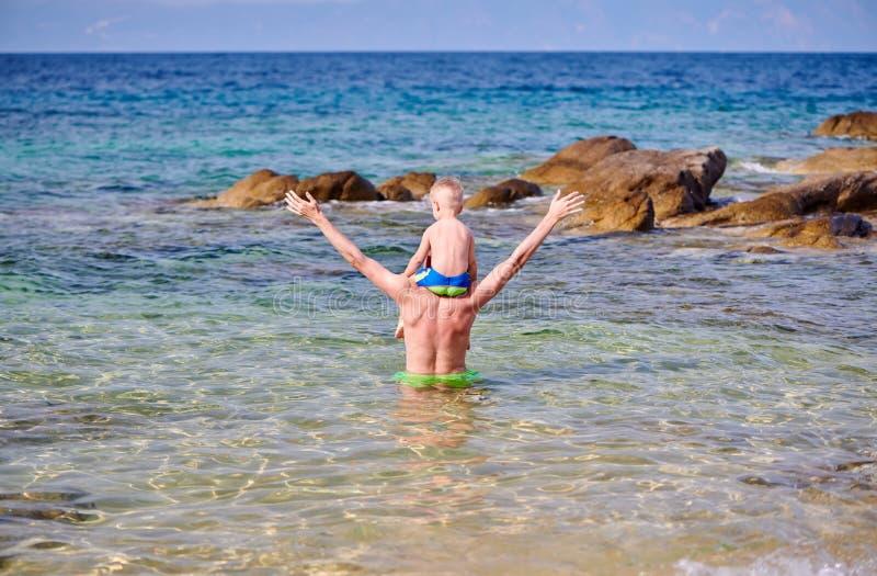 Menino da crian?a nos ombros do pai na praia fotos de stock royalty free