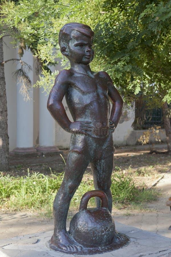 Menino da escultura com pesos na terraplenagem de Gorky em Evpatoria, imagem de stock royalty free