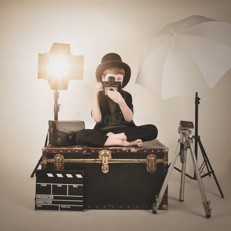 Menino da fotografia de Vinatge com câmera e luzes velhas foto de stock royalty free