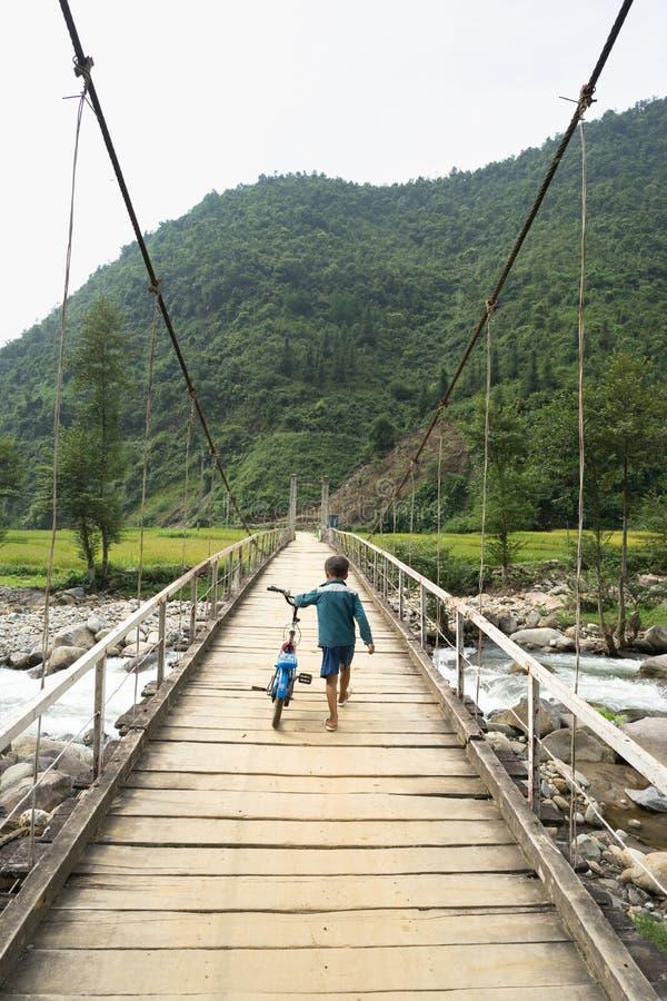 Menino da minoria étnica de Hmong do vietnamita que anda na ponte de madeira velha com sua bicicleta imagens de stock