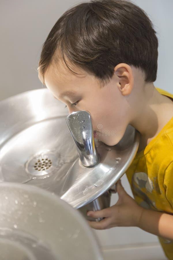Menino da raça misturada que bebe da fonte de água fotos de stock royalty free