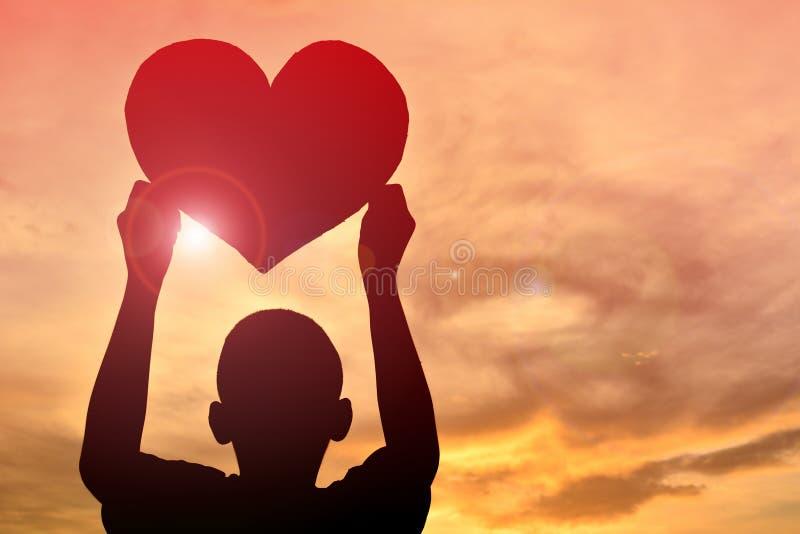 Menino da silhueta que guarda a forma do coração imagens de stock royalty free