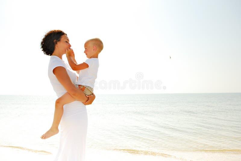 Menino da terra arrendada da mulher na praia fotos de stock royalty free