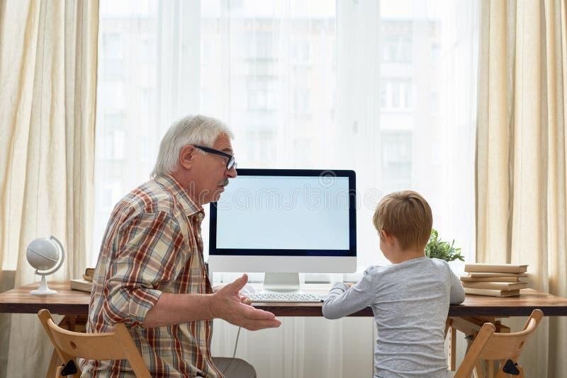 Menino de ajuda do vovô com trabalhos de casa foto de stock royalty free