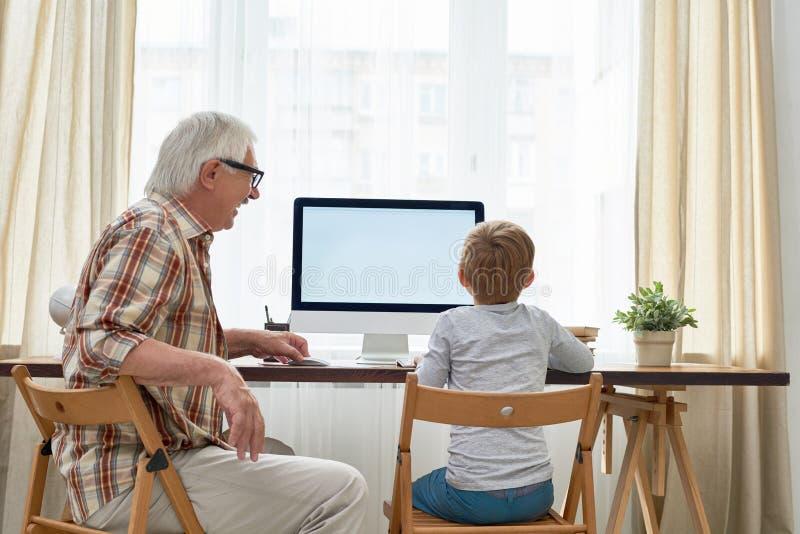 Menino de ajuda do vovô com trabalhos de casa imagem de stock