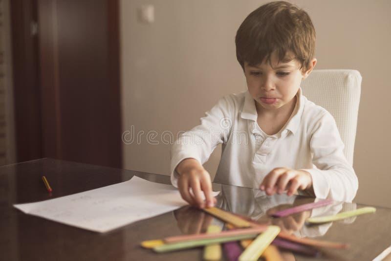 Menino de 4 anos faz lição de casa em casa Ele faz operações de adição e subtração com paus fotografia de stock
