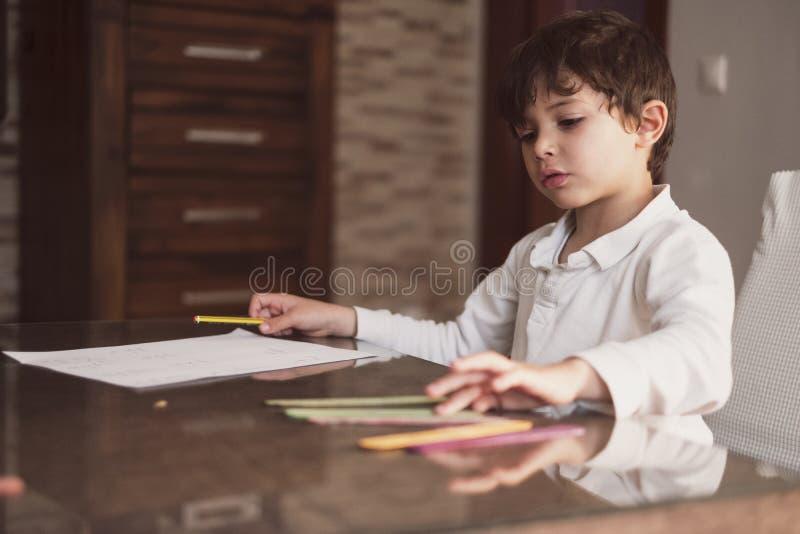 Menino de 4 anos faz lição de casa em casa Ele faz operações de adição e subtração com paus imagem de stock