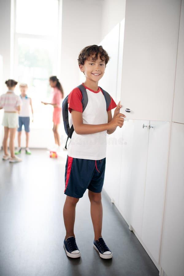 Menino de cabelo escuro vestindo roupas esportivas em pé perto do armário imagens de stock royalty free
