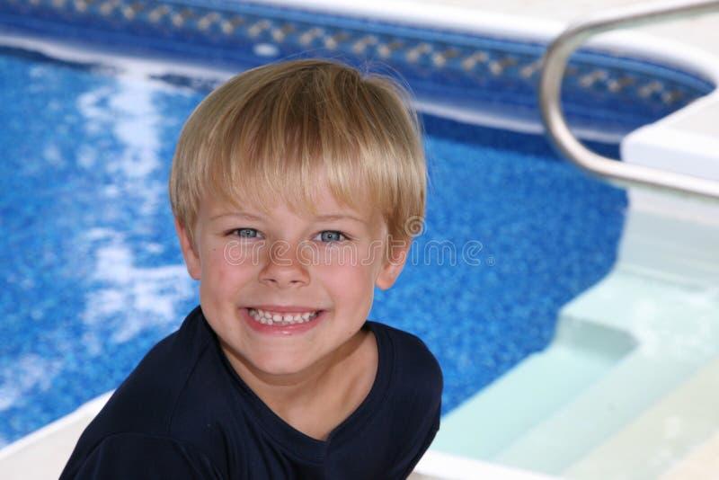 Menino de cabelo louro ao lado da piscina fotografia de stock