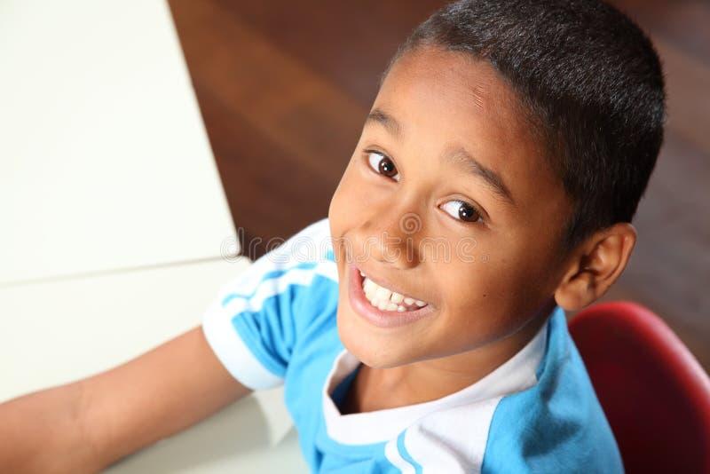 Menino de escola étnico alegre novo 9 na sala de aula fotografia de stock
