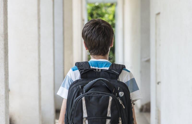 Menino de escola adolescente com uma trouxa no seu parte traseira que anda à escola fotos de stock