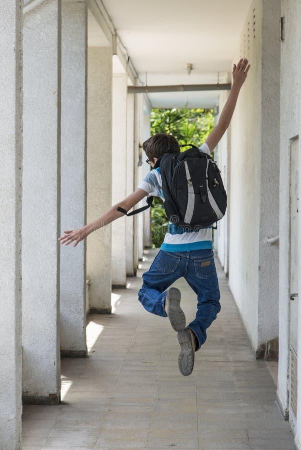 Menino de escola adolescente com uma trouxa no seu parte traseira que anda à escola fotos de stock royalty free