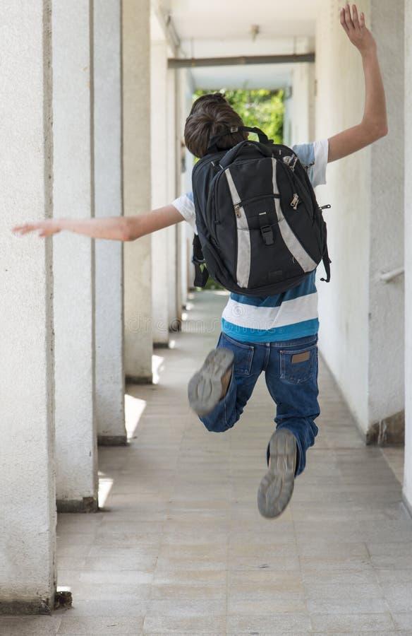 Menino de escola adolescente com uma trouxa no seu parte traseira que anda à escola foto de stock royalty free