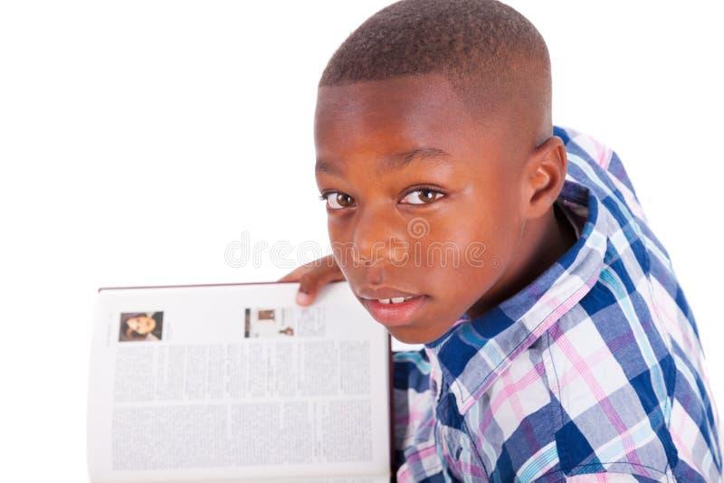Menino de escola afro-americano que lê um livro - pessoas negras imagens de stock