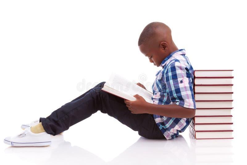 Menino de escola afro-americano que lê um livro - pessoas negras imagem de stock royalty free