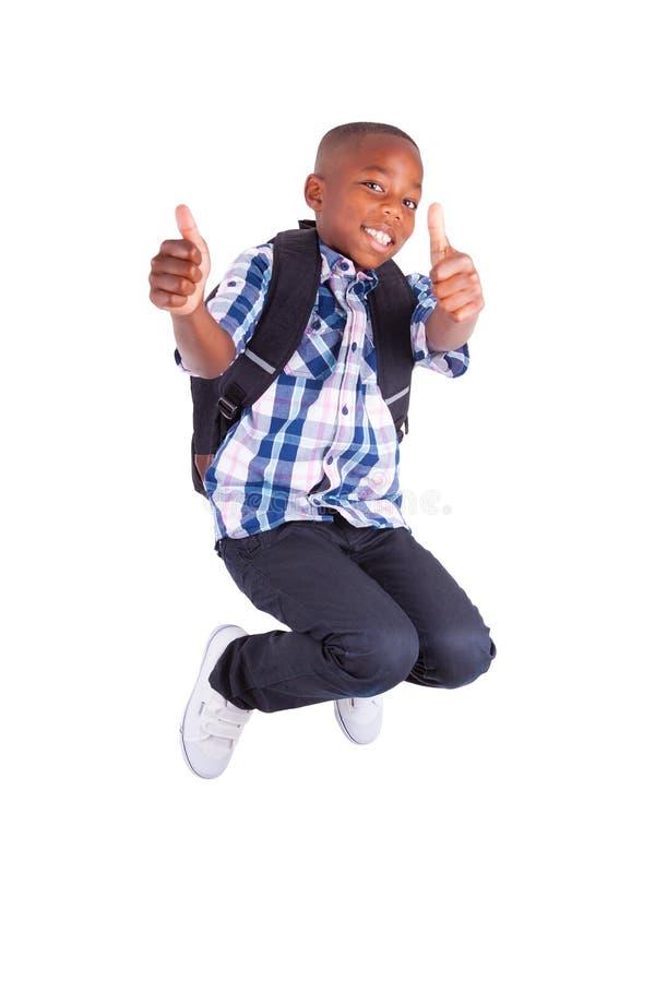Menino de escola afro-americano que salta e que faz o preto dos polegares acima - imagem de stock royalty free