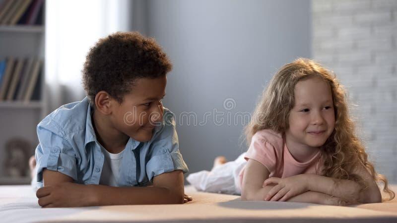 Menino de escola americano que olha a menina bonito, passando o tempo junto, amizade foto de stock royalty free