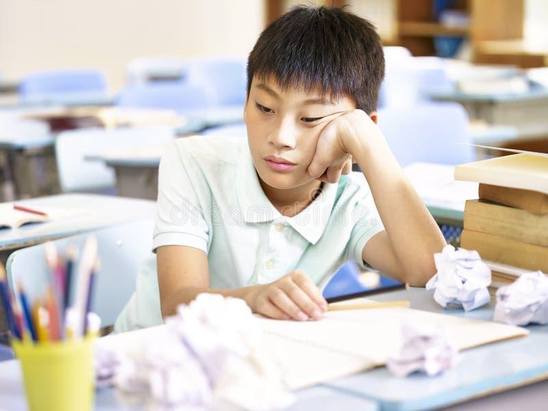 Menino de escola asiático frustrante fotografia de stock