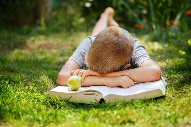 Menino de escola bonito que encontra-se em uma grama verde que não queira ler o livro menino que dorme perto dos livros foto de stock royalty free