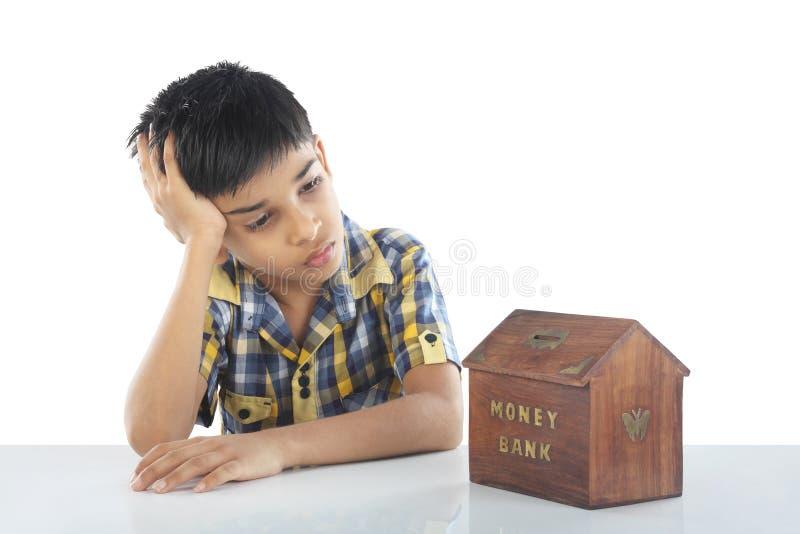 Menino de escola deprimido com mealheiro fotografia de stock