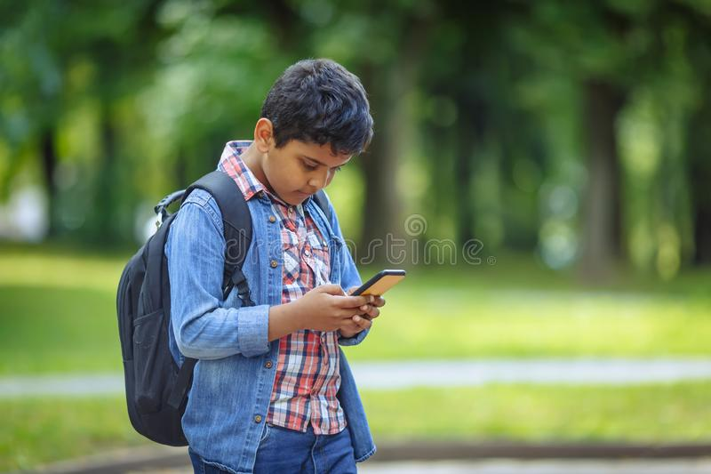 Menino de escola feliz do afro-americano exterior do retrato com smartphone Estudante novo que olha o telefone celular De volta ? imagens de stock royalty free