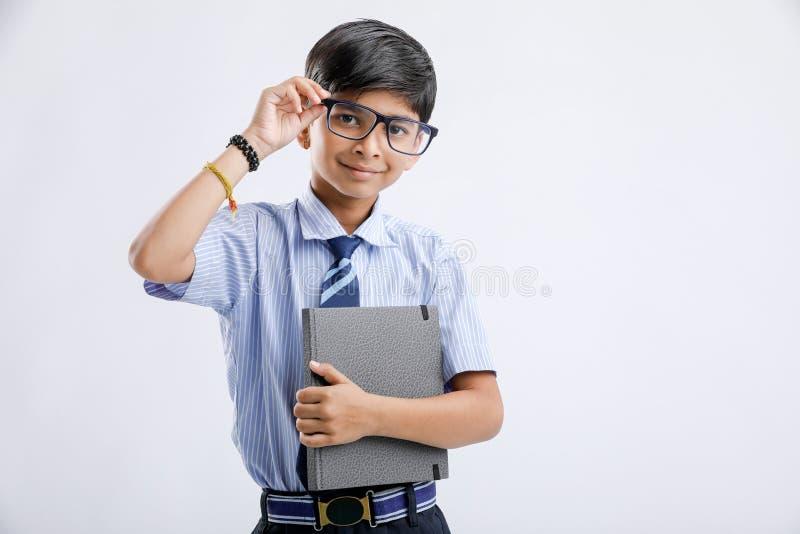Menino de escola indiano/asiático pequeno bonito com o livro de nota isolado sobre o fundo branco imagem de stock