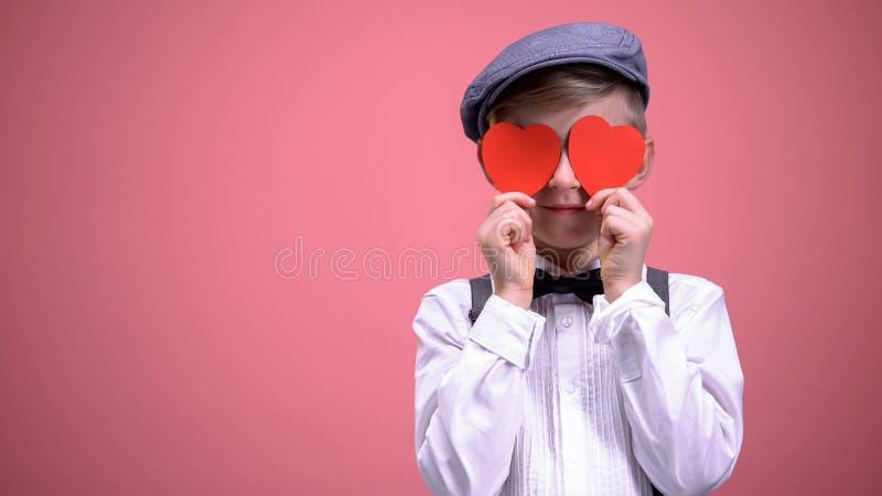 Menino de escola na roupa do vintage que fecha os olhos com corações vermelhos no feriado dos Valentim fotos de stock