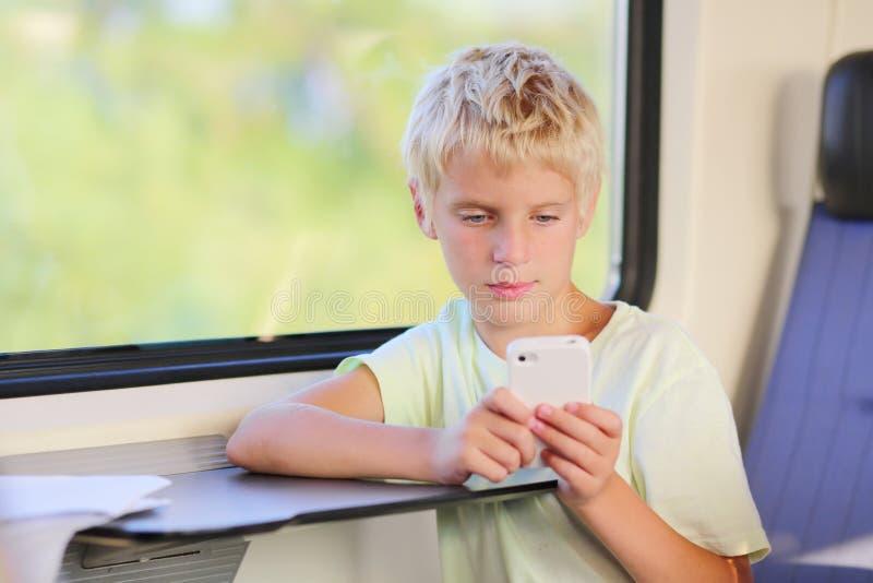 Menino de escola novo no trem com telefone celular fotografia de stock