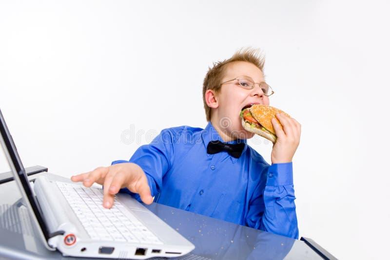 Menino de escola novo que come o Hamburger fotos de stock