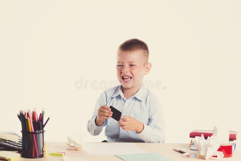 Menino de escola pequeno bonito com a cara triste que senta-se em sua mesa no fundo branco Crianças inteligentes infelizes na cam imagens de stock