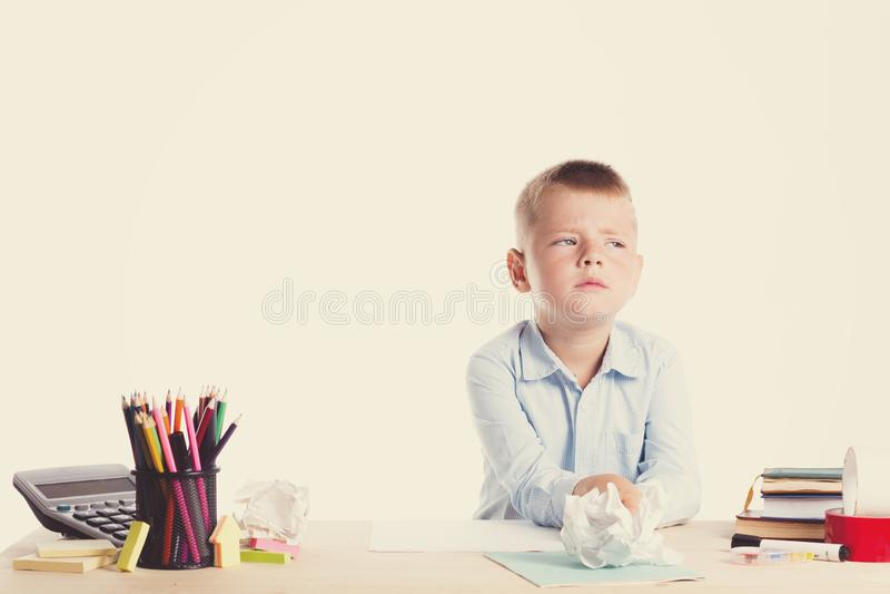 Menino de escola pequeno bonito com a cara triste que senta-se em sua mesa no fundo branco Crianças inteligentes infelizes na cam imagem de stock