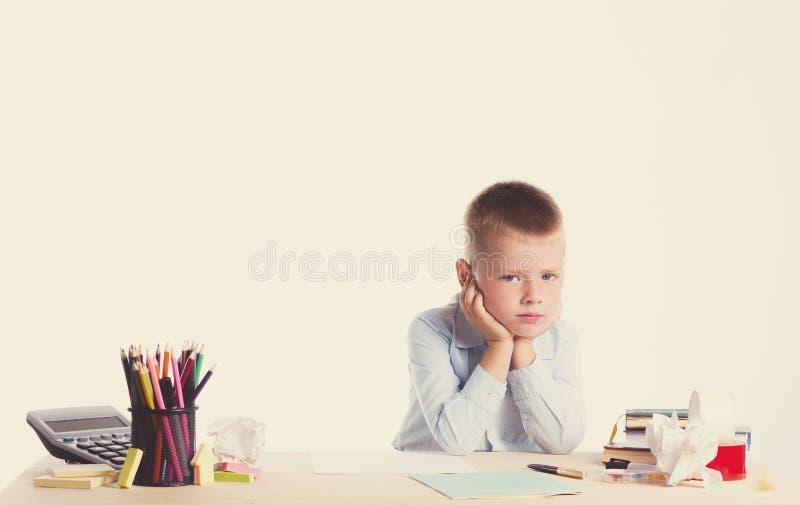 Menino de escola pequeno bonito com a cara triste que senta-se em sua mesa no fundo branco Crianças inteligentes infelizes na cam foto de stock royalty free