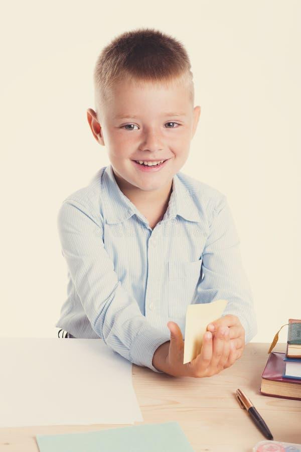 Menino de escola pequeno bonito com o sorriso enorme que senta-se em sua mesa no fundo branco Crianças inteligentes felizes na ca fotografia de stock