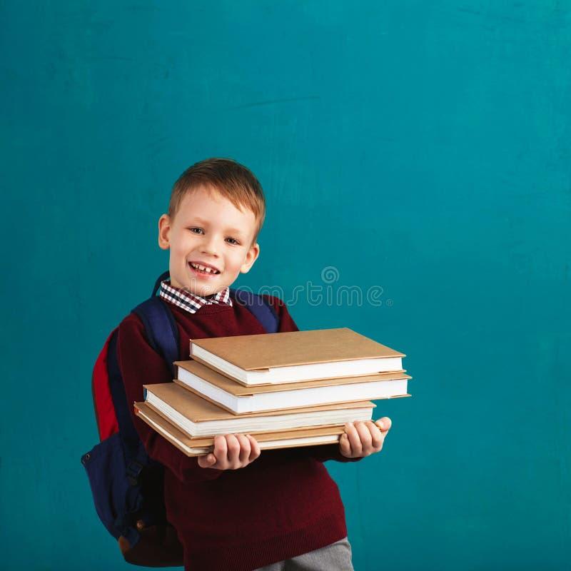 Menino de escola pequeno pensativo alegre na farda da escola com CCB fotos de stock royalty free