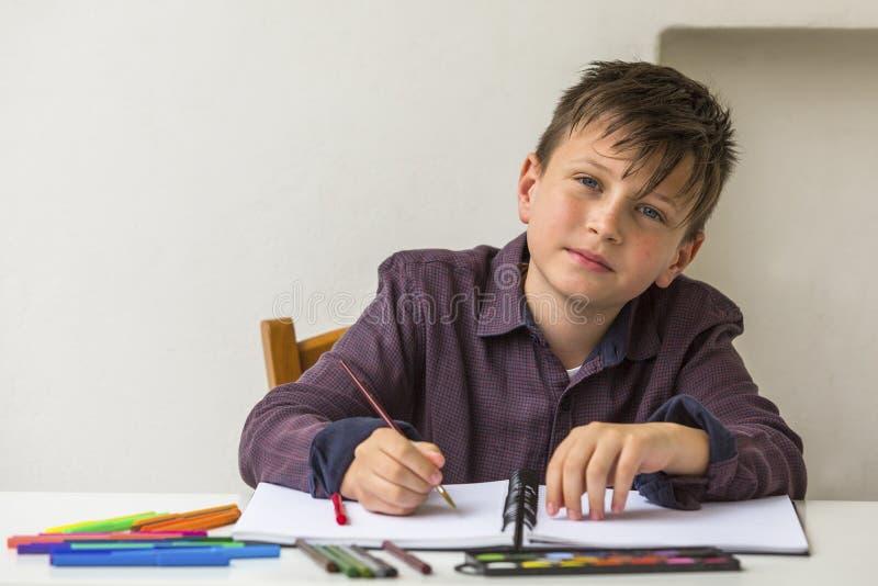 Menino de escola que faz trabalhos de casa em sua mesa Retrato foto de stock