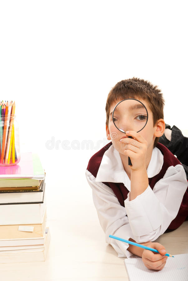 Menino de escola que olha durante todo a lupa foto de stock royalty free