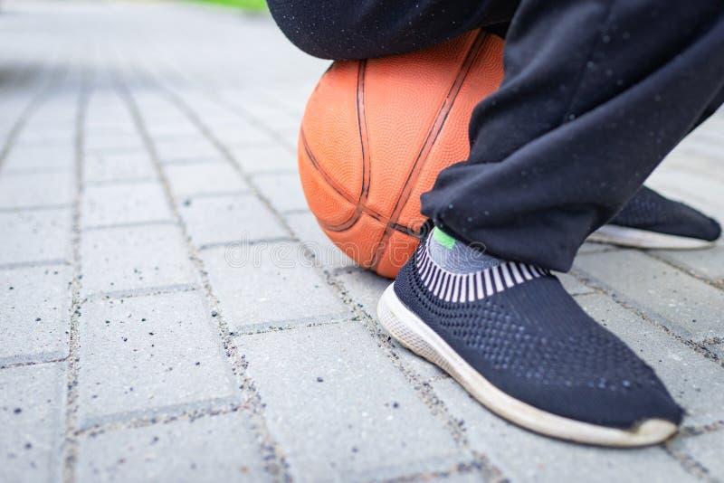Menino de escola que senta-se no basquetebol imagem de stock royalty free