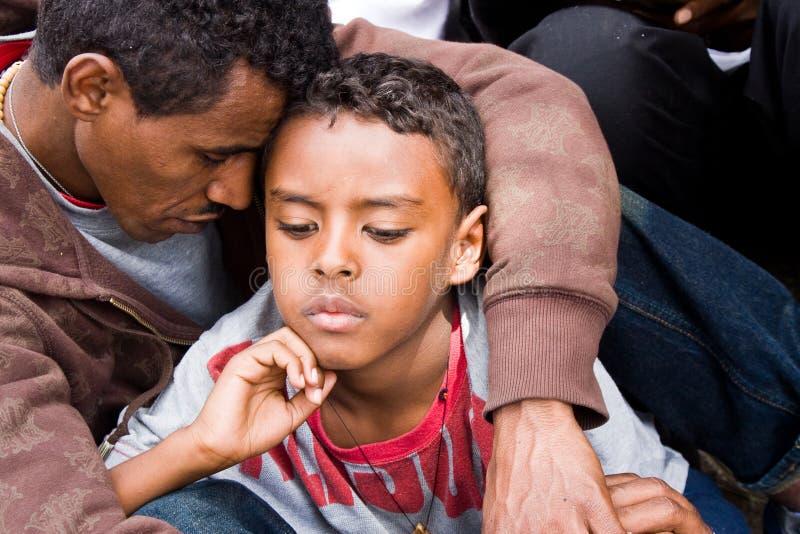 Menino de Ethiopean e seu pai no serviço de Easter imagem de stock royalty free
